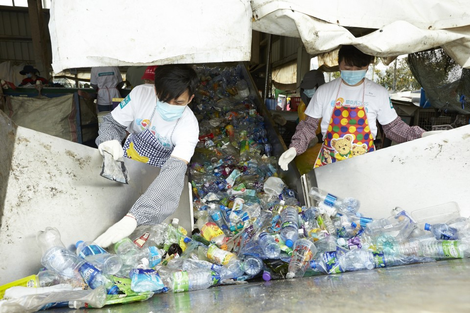 來自屈臣氏義工隊的義工正在為塑膠容器分類
